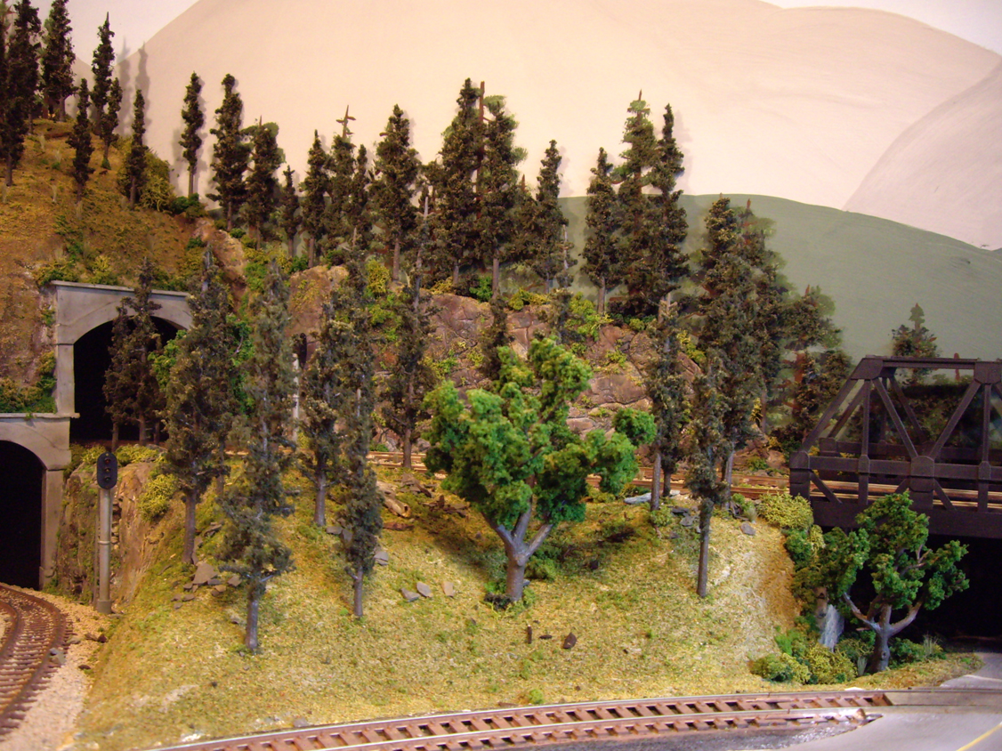 Completed forest scene near a tunnel entrance made with various ground foam, trees, talus and field grass