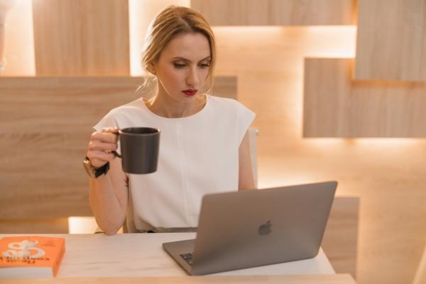 Mulher sentada à mesa em frente ao notebook tomando seu café matinal