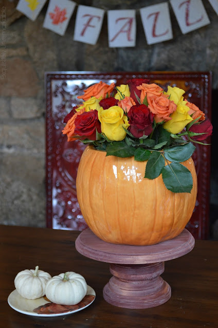 Easy DIY wooden cake stand with cookie jar flower vase on top in front of a fireplace