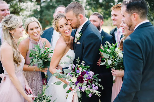 groom kisses bride surrounded by wedding party