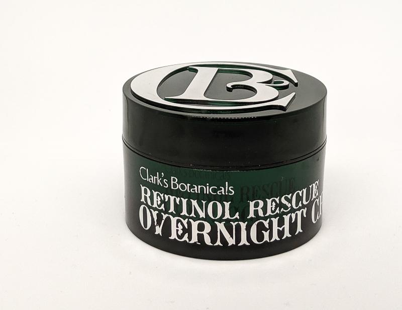 Jar of Clark's Botanicals Retinol Rescue Overnight Cream. The jar is dark green with white writing