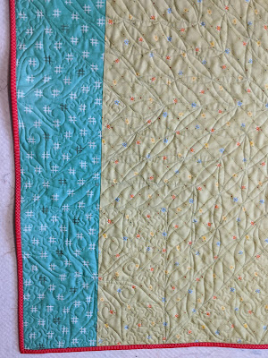The quilt back highlights details of the free motion quilting