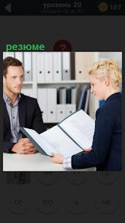 За столом мужчина и женщина читает составленное им резюме
