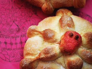 A closeup of a Pan de Muerto (Bread of the Dead) roll. It is decorated with a red skull on top and sits on a pink cloth.
