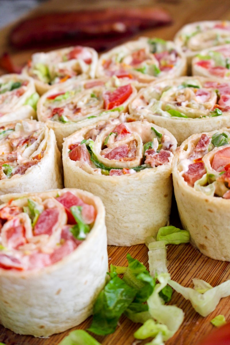 Side view of Bacon, Lettuce, and Tomato Pinwheels on a cutting board.