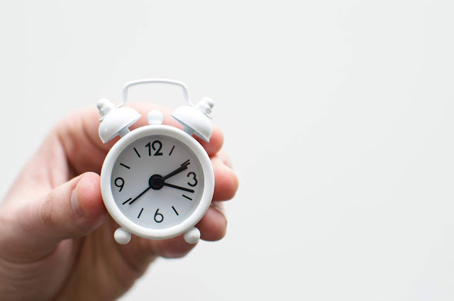 A hand holds a small white traditional style alarm clock.