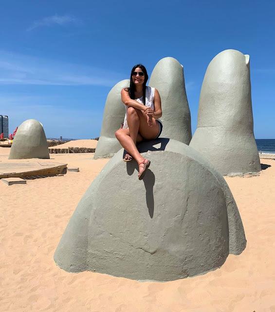 mulher em cima do polegar da escultura de los dedos na praia brava de punta del este