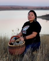 A brunette woman standing in a field with a large basket full of plants. There is a lake in the background, Linda Black Elk