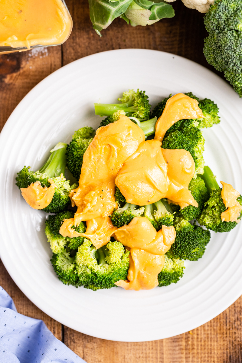 Over head photo of Easy Keto Cheese Sauce over broccoli on a white plate.