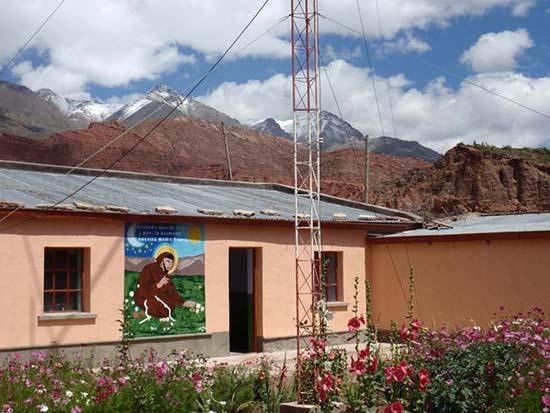 Mein Pfarrhaus mit Blumengarten im Hintergrund die Schneeberge der Anden