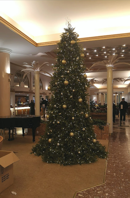 Valmis koristelemamme aulan kultakoristeinen iso joulukuusi.
