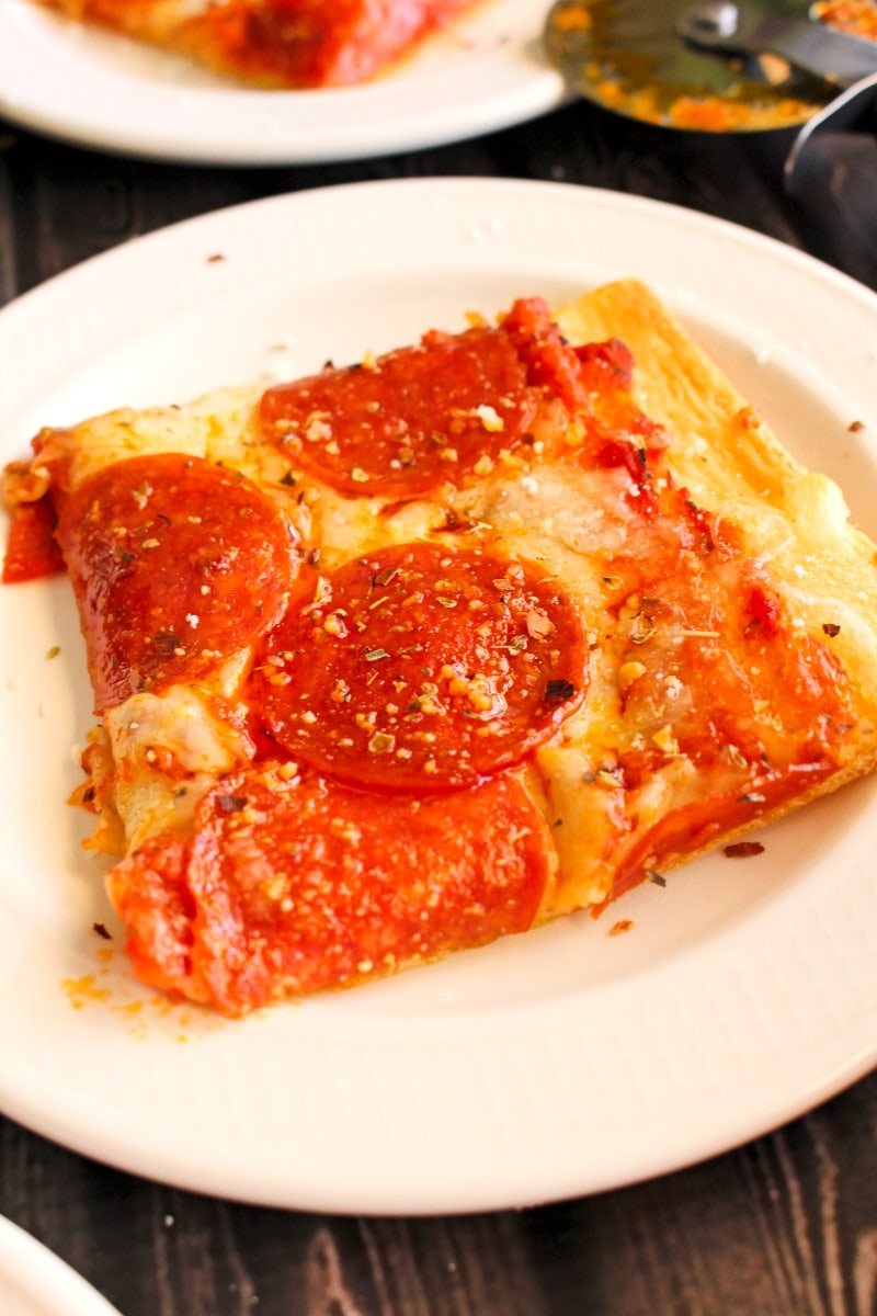 Close up side view of a square piece of pepperoni pizza on a white plate.