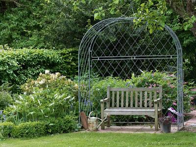 Ein gemütlicher Sitzplatz unterm Rosenbogen, der mit Clematis bepflanzt wird .