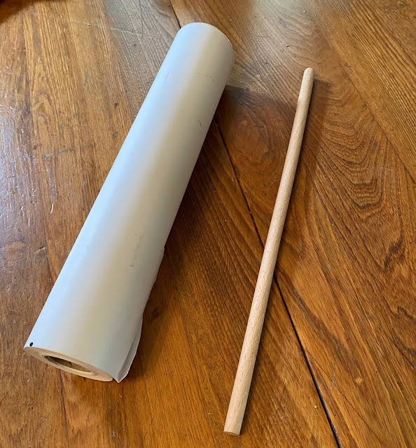 Photo of a roll of white paper and a dowel