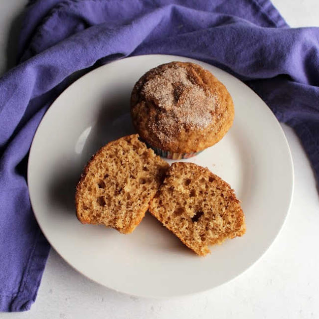 plate with one whole muffin with cinnamon sugar top and another cut in half showing airy center and light brown color