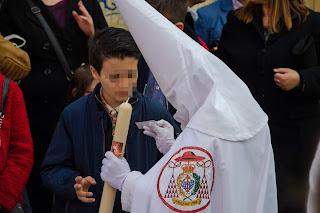 Niño pidiendo estampitas a un nazareno