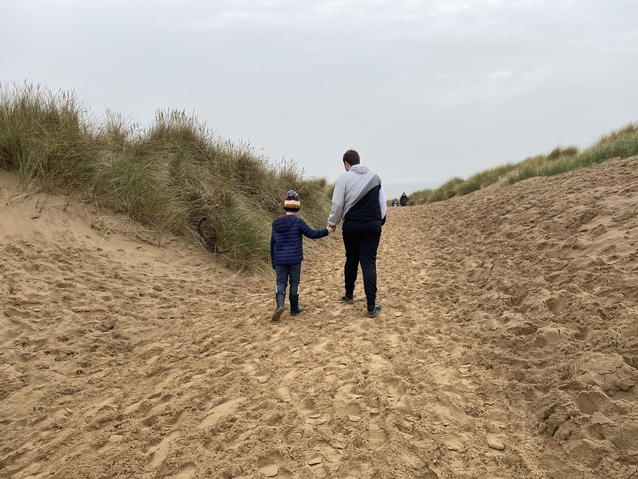 boys walking over Sand Dunes