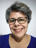Mulher, sorridente, com batom vermelho, cabelos grisalhos e usando óculos