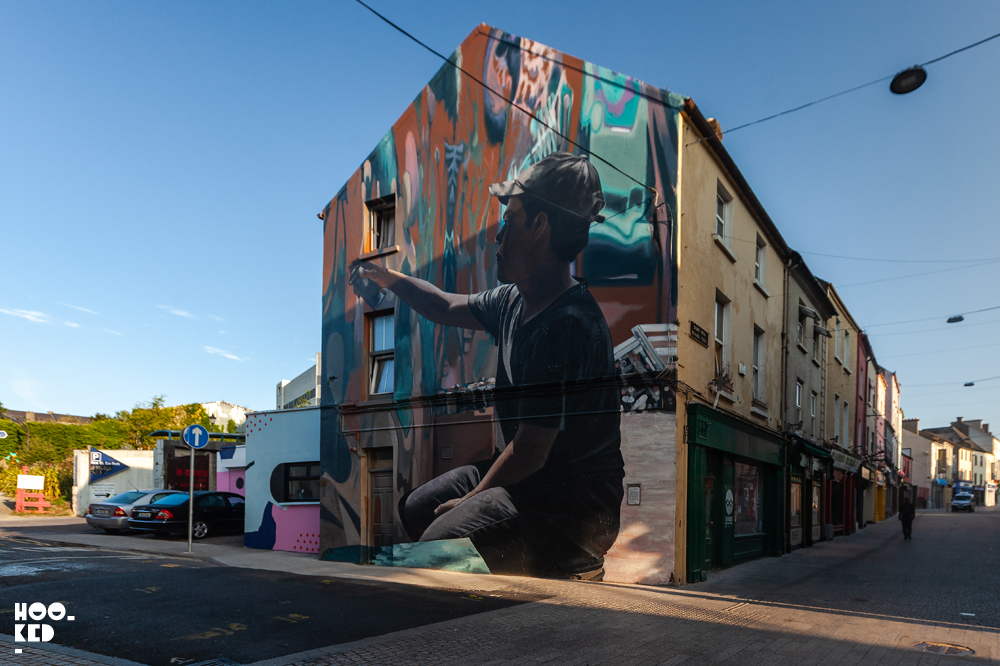 Mural featuring a kneeling Boy spray painting by French street artist Mantra