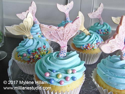 Platter of vanilla cupcakes iced with blue buttercream icing, sprinkled with pastel coloured rice pearls and topped with a mermaid's tail.