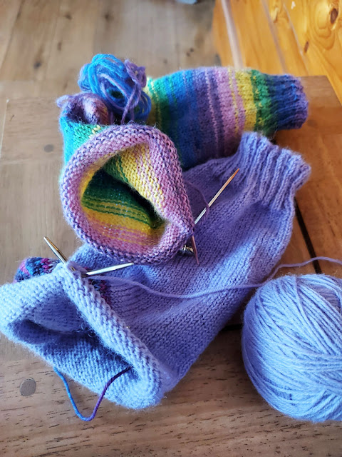 Two half-knitted socks on a wooden table.  The top sock is multicoloured and the bottom sock is purple