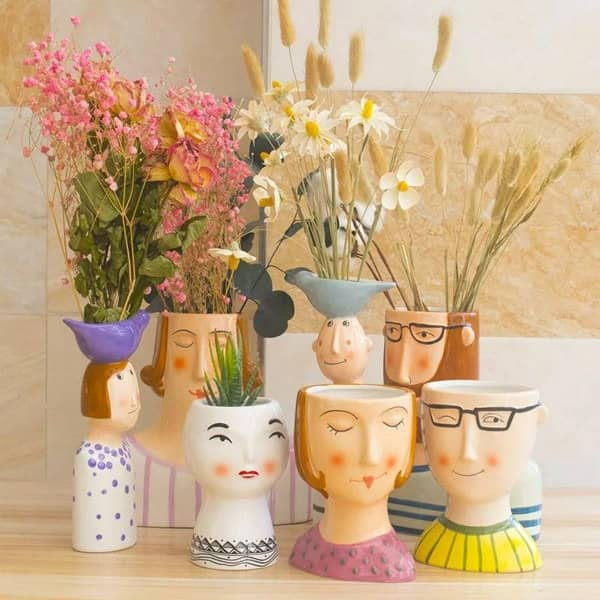 ceramic family character vases holding a floral arrangement in each one