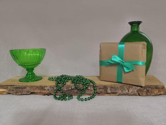 Vihreä muovikulho, puualusta, vihreä helmikoru, ruskea lahjapaketti vihreällä satiininauhalla ja vihreä lasimaljakko.