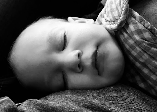 a black and white close up photograph of a baby held by his mother while he sleeps