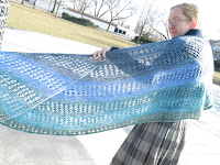 A woman wearing a garter stitch and lace crescent shawl. The shawl is striped in a blue-green gradient. One edge of the shawl is out of frame, with the other end wrapped around her shoulder, with the wingspan held open.