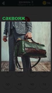 в руке у мужчины небольшой саквояж зеленого цвета