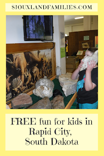 "at top, ""SiouxlandFamilies.com"". in center, a photo of a boy who is holding a large shell up to his ear while looking at a display of rocks and fossils. at bottom, the words ""FREE fun for kids in Rapid City, South Dakota"""