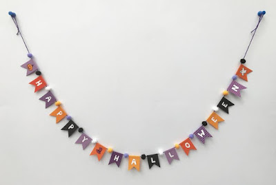 A string of bunting saying Happy Halloween with pom poms between each letter