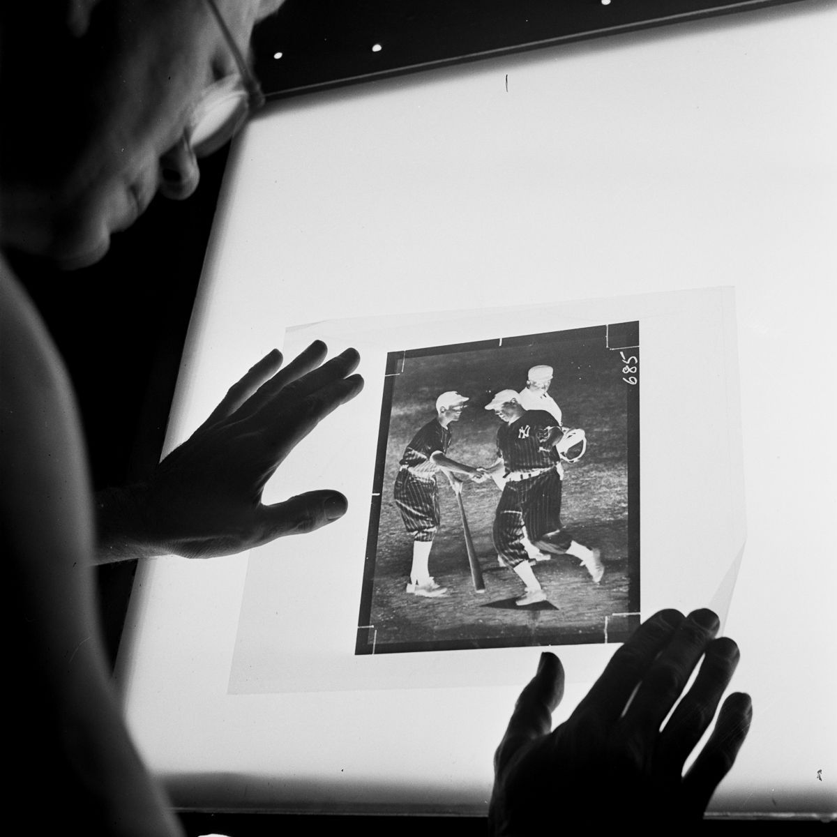 A darkroom technician inspects the dots on the screen of a strip negative before it is transferred to a zinc plate.