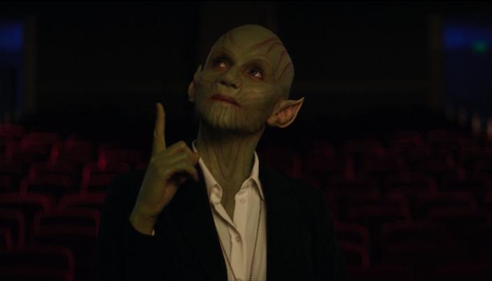 Imagem: a personagem Skrull, verde, careca e com orelhas pontudas e olhos azuis em um terno, olhando para cima e apontando para o dedo. Ao fundo uma sala de cinema com poltronas vermelhas e um projetor ligado.