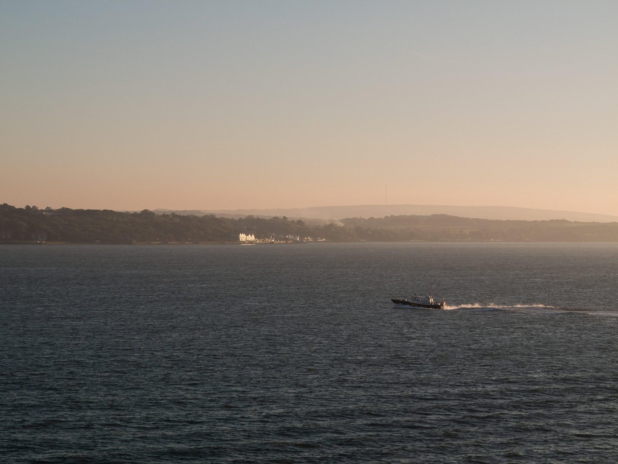 A boat sailing across the Solent at golden hour.
