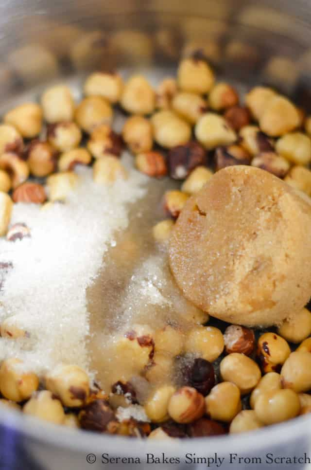 Peeled Hazelnuts in pan with brown sugar, granulared sugar, and water.