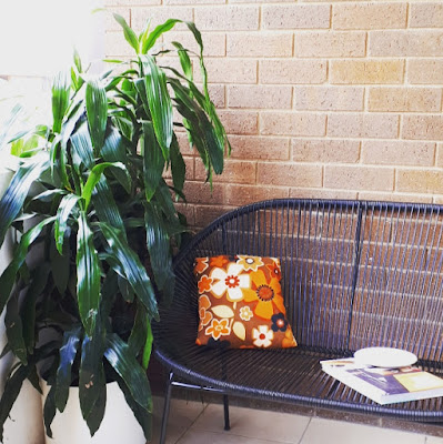 Balcony with two large pot plants next to a mid-century modern wire sofa. On the sofa is a bright flowery cushion, a book and a plate.