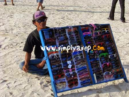 PENJUAL KACA MATA : Penjual Kaca mata di pantai Kuta ini ternyata mahir menggunakan bahasa Inggris untuk memperlancar jualan dagangannya. Foto Asep Haryono