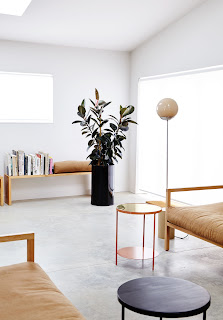 bench with books and cushion, shiny black modern planter, free-standing floor lamp with neutral milk glass bulb, small round nesting accent tables