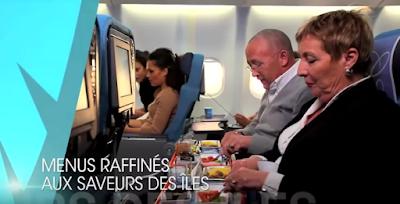 Couple senior en classe Premium Air Caraibes devant un plateau repas