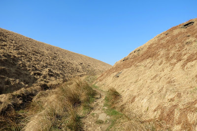Pale moorland grasses on the side of the clough and a narrow path leading into this small valley. Cloudless blue skies above.
