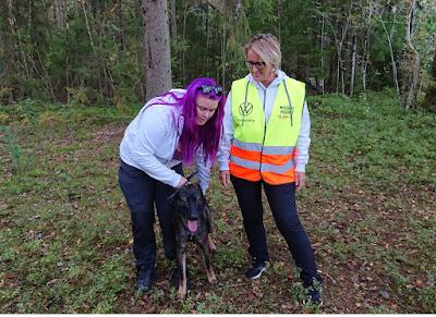 Linnéa Awwö Andersson och Susanna Johansson med hunden Herax framför sig i skogsmiljö.