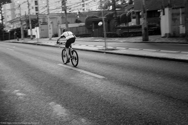 Ciclista circulando em via exclusiva para ônibus e acima da velocidade permitida.