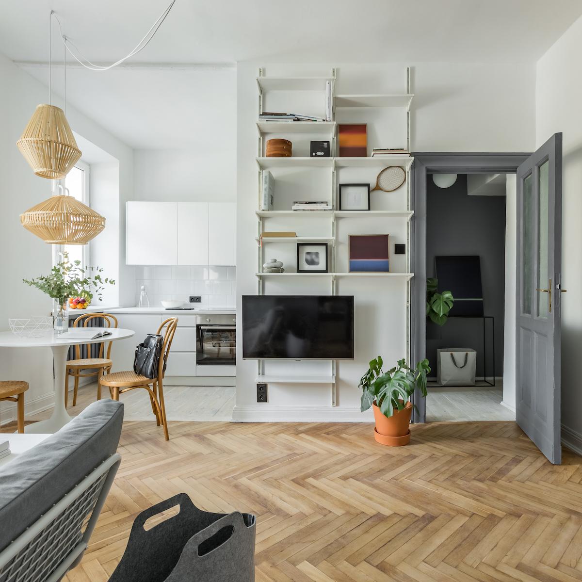Salón con paredes blancas, suelo de madera y muebles claros