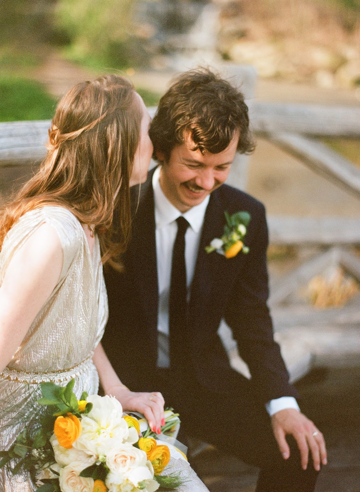 intimate moment between bride and groom in prospect park, brooklyn, new york with yellow ranunculus and white peony spring bouquet and boutonniere