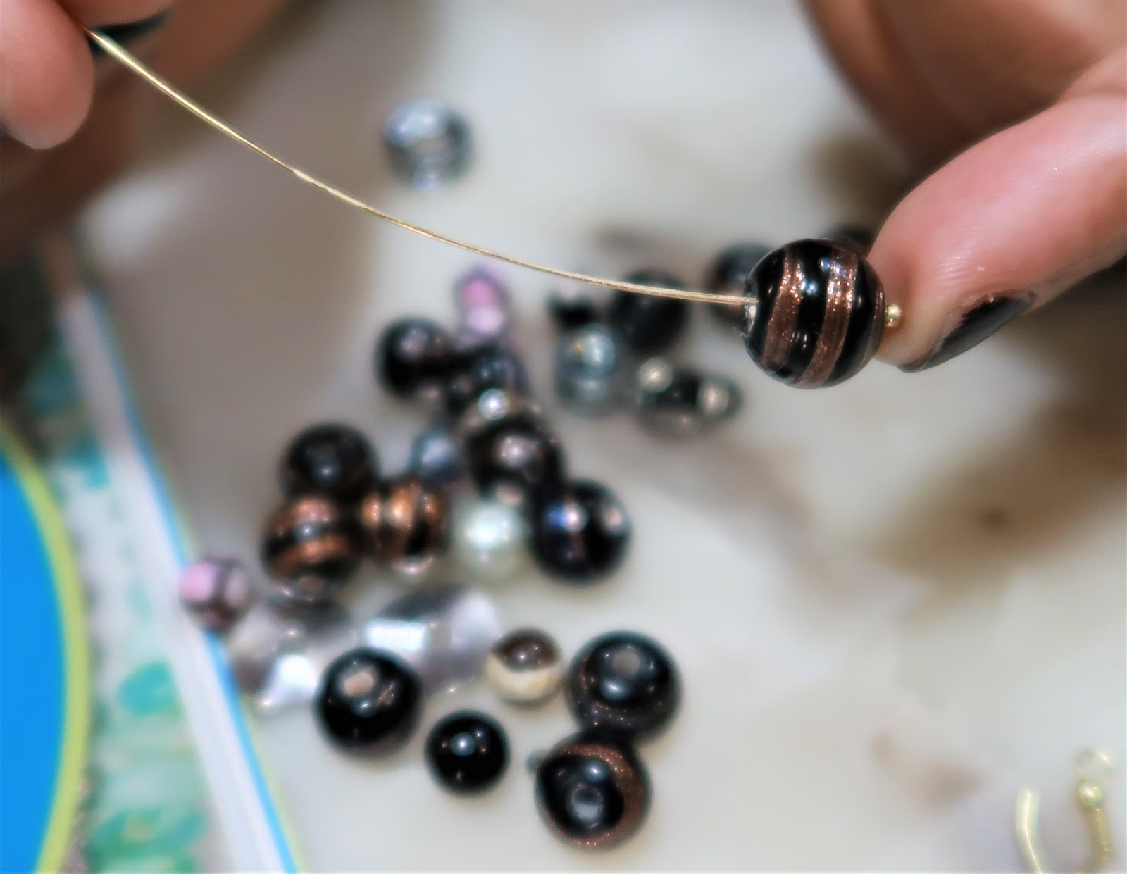 Image: Tangie showing how to use beads and other things to make earrings. Seen first on Bits and Babbles Blog.