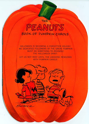 "This is a screenshot of an image from a post (October 6 2020) on the FB Page for The Charles M  Schulz Museum (https://www.facebook.com/schulzmuseum/posts/10158900795653054. The songbook is orange and in the shape of a pumpkin. A listing of ""pumpkin carols"" is printed on it and below that list is a drawing of the PEANUTS gang (at the left Lucy, Schroeder and Charlie Brown are standing as they look on at Linus and Snoopy)."