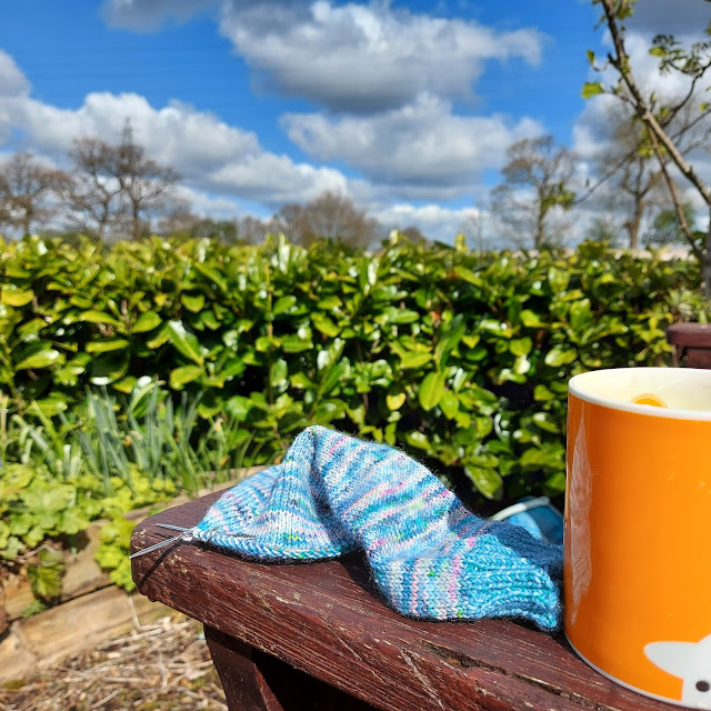 A blue speckled sock on a circular needle rests on arm of a wooden garden bench next to an orange mug.  In the background is a hedge.
