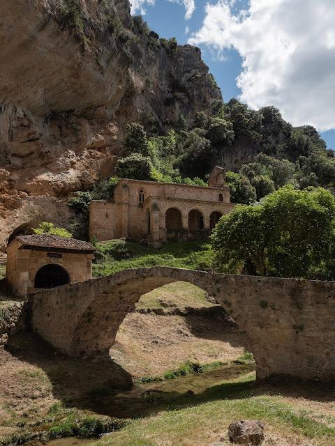 Puente romano medieval con ermita encajada en una montaña