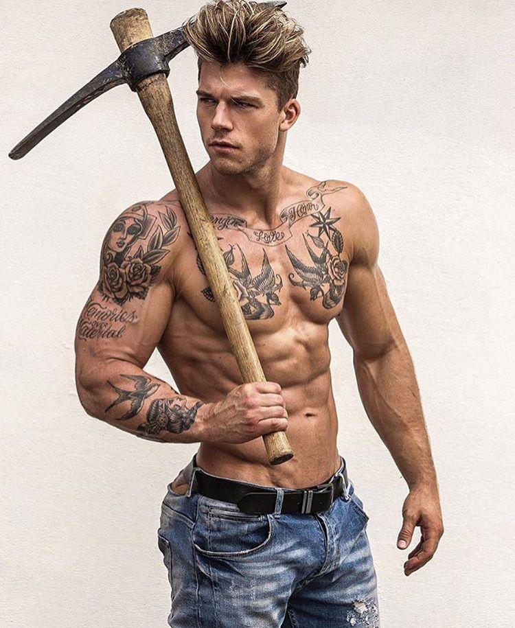 Foto de un joven musculoso posando con pico, lleva tatuajes de la vieja escuela